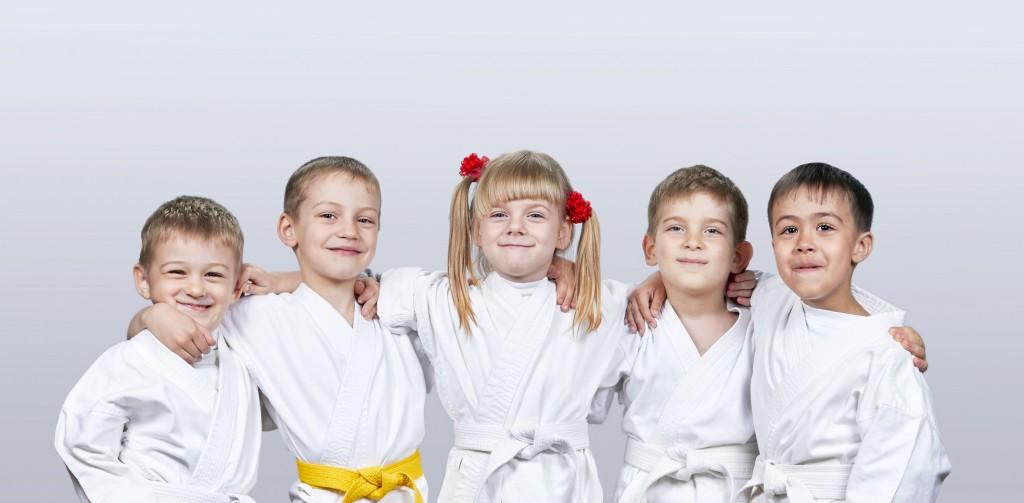 Cheerful children in karategi on a gray background