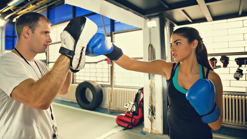 Instructor Teaching Young Woman Boxing